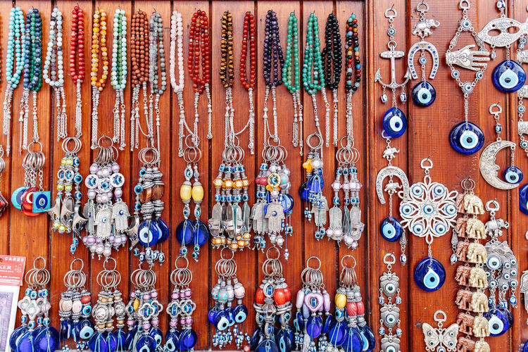 Various jewelry hanging on wooden wall at market