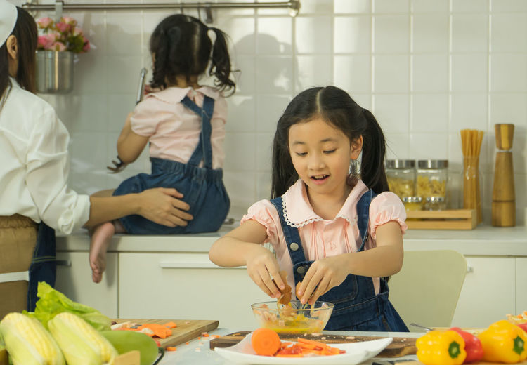 Happy friends and vegetables in kitchen at home
