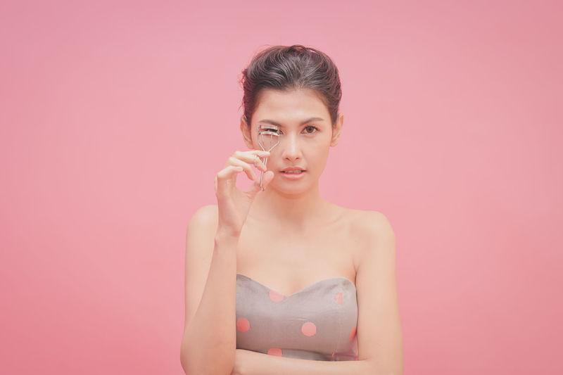 Portrait of woman holding eyelash curler against pink background