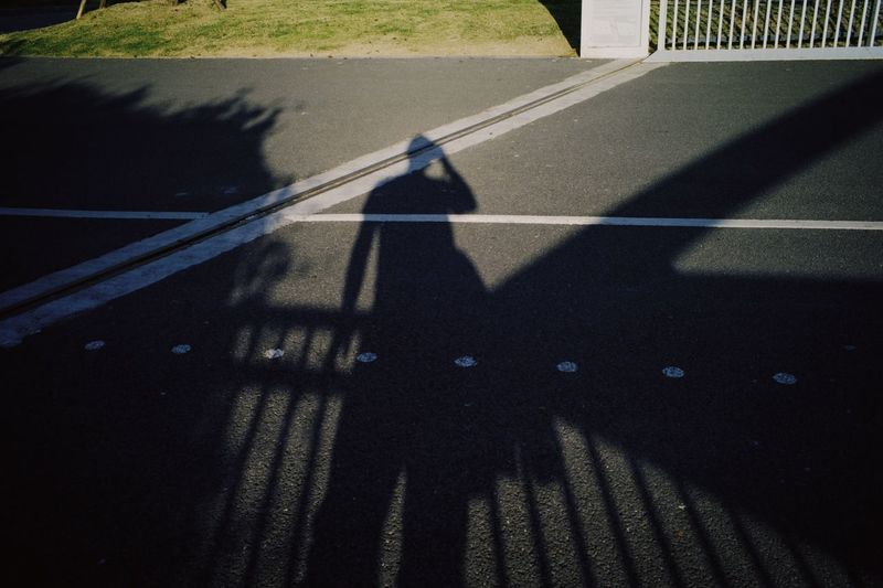 Shadow of people riding motorcycle on road