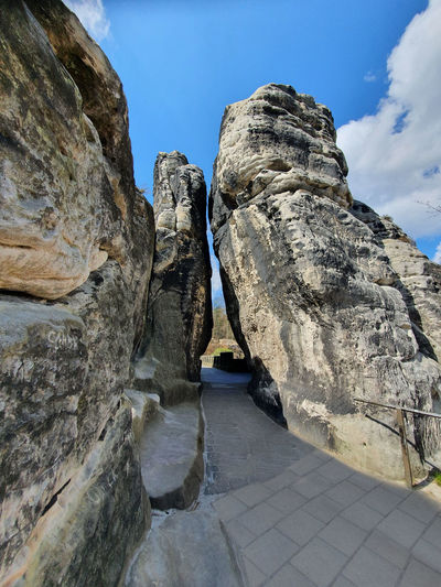 Low angle view of rocks on footpath against sky