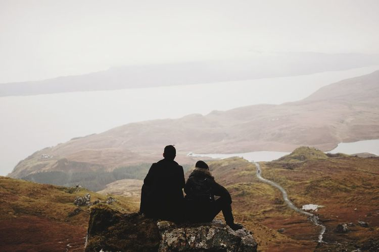 Couple sitting on top of rock