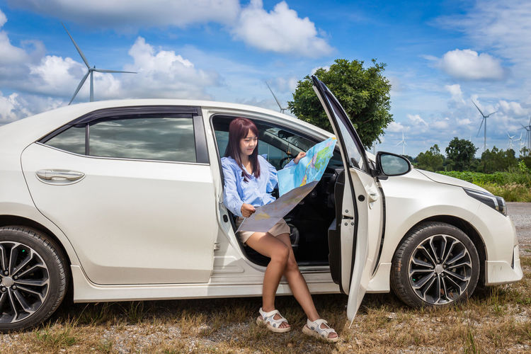 Woman holding map sitting in car