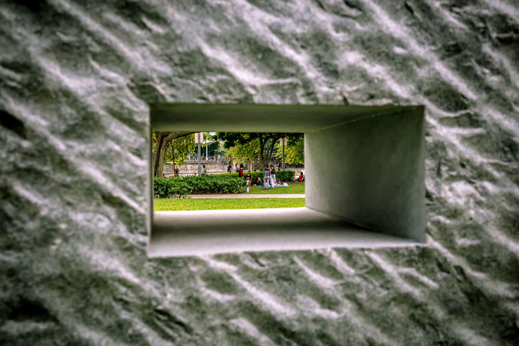 I was trying to get a shot through these wall sculptures and found a gathering instead. Group Of People Gathering Hole In The Wall Wall Built Structure Close-up Day Grass Hole No People Park - Man Made Space Sculpture Selective Focus Tree A New Perspective On Life