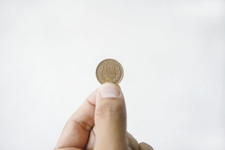 Close-up of hand holding coin against white background
