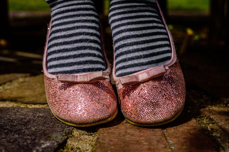 Low section of woman wearing pink shoe