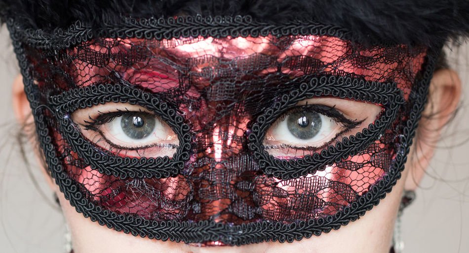 Close-up portrait of woman wearing red masquerade mask