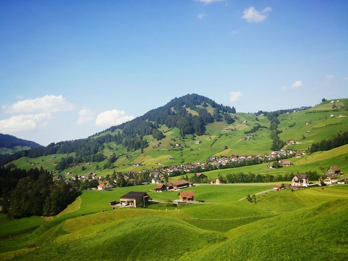 Made in Swiss! Switzerland Landscape Agriculture Rural Scene Mountain Tranquil Scene Tranquility Green Color Sky Village Nature Non-urban Scene Blue House Farm Scenics Green Field Swiss Alps Alpes Mountains Iconic