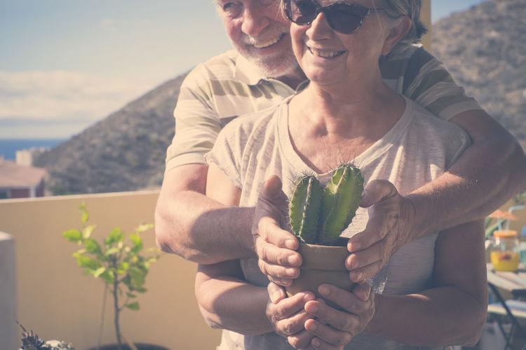 Senior Couple Holding Potted Cactus Plant