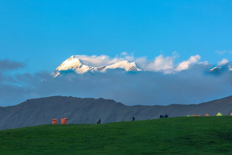 """Trishul"" After waiting for an hour for the clouds to clear, the campers enjoy this mesmerising view which shook them from within. Location - Bedni Bugyal, Himalayas. The Great Outdoors - 2018 EyeEm Awards The Traveler - 2018 EyeEm Awards Sky Mountain Cloud - Sky Landscape Scenics - Nature Environment Beauty In Nature Mountain Range Land Nature Tranquility Plant Tranquil Scene Field No People Agriculture Day Grass Green Color Blue"
