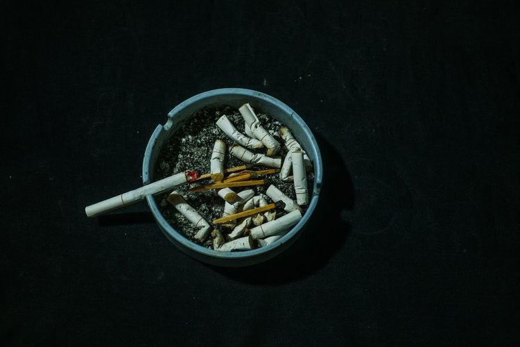 Close-up of cigarette on table against black background