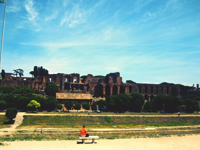 Rear View Of Man Sitting In Front Of Circus Maximus Against Blue Sky
