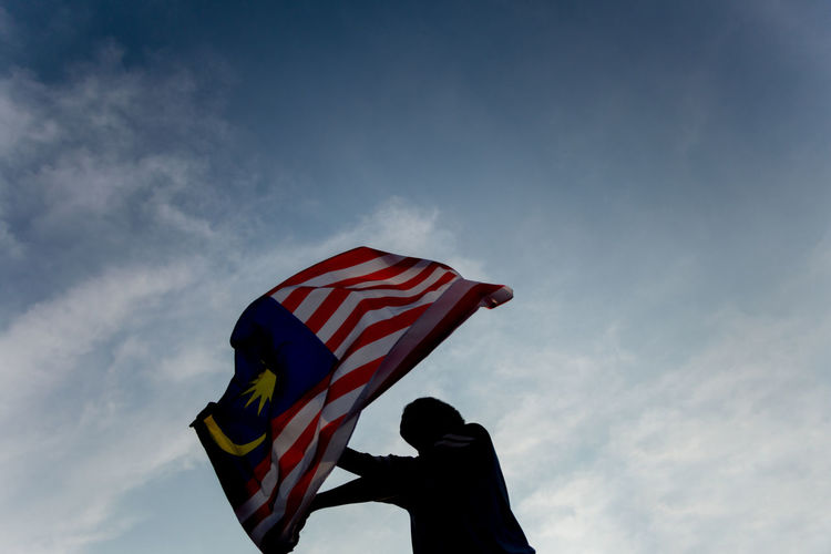 A boy is waving Malaysian flag ASIA August Cloud Independence Patriotic Patriotism Silhouette Waving Waving Flag Boy Flag Holding Independence Day Malaysia Merdeka Month Sky