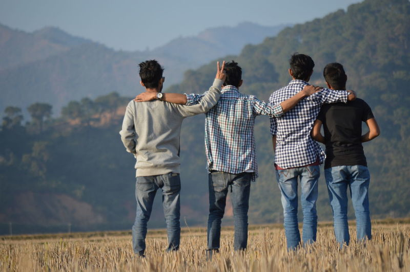 Rear view of friends standing on grassy field against mountains