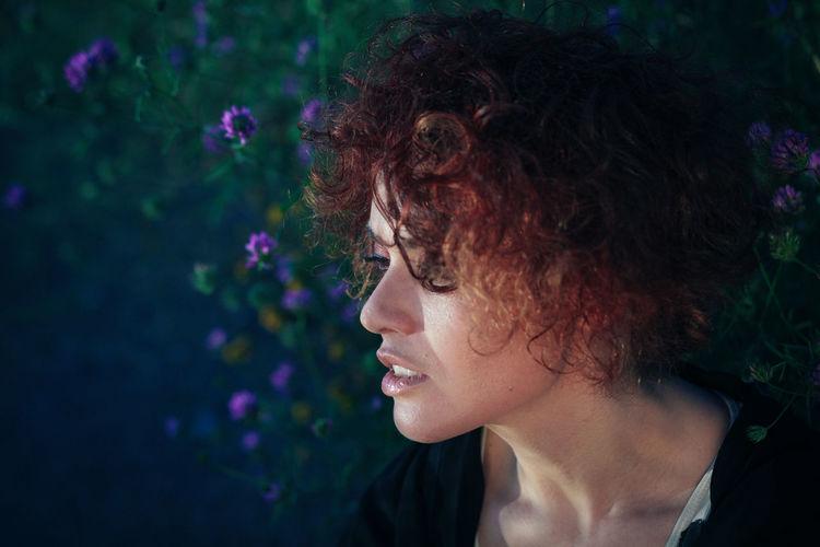Woman Looking Away Against Purple Flowers