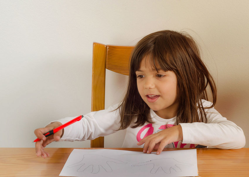 5 years girl doing educational exercises on a blank white paper Childhood Close-up Crayon Day Drawing - Activity Elementary Age Girls Headshot Holding Human Hand Indoors  One Person Paper People Real People Sitting Table Wood - Material