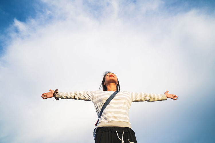 Low angle view of woman with arms outstretched standing against sky