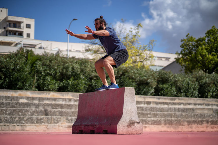 Woman jumping against built structure