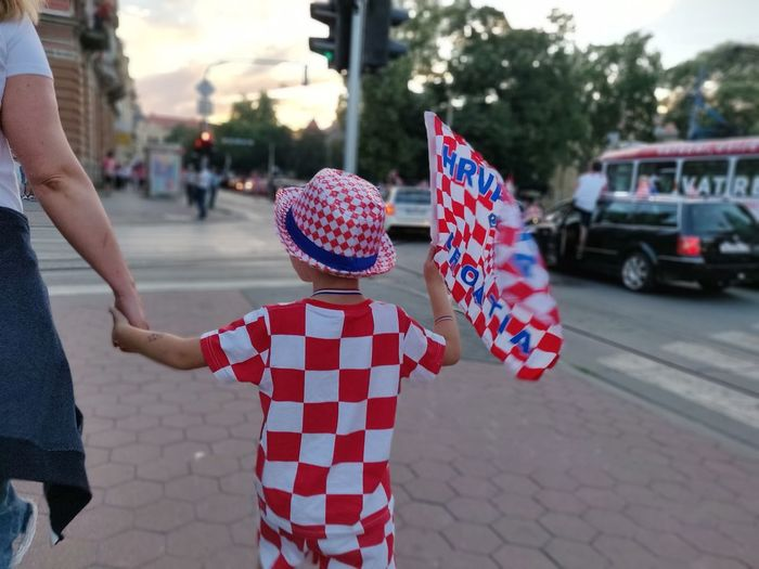 Rear view of boy carrying croatian flag while walking with mother in city