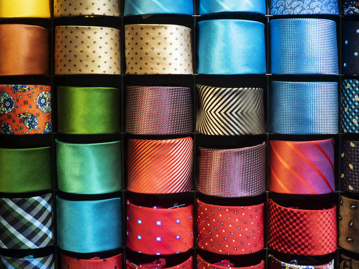 Showcase with multicolored ties Display Multicolored Tie Men Pattern Full Frame Indoors  Backgrounds No People Arrangement Side By Side Still Life In A Row Choice Large Group Of Objects Stack Variation Order Multi Colored Close-up Retail  Textile For Sale Abundance Spool Retail Display