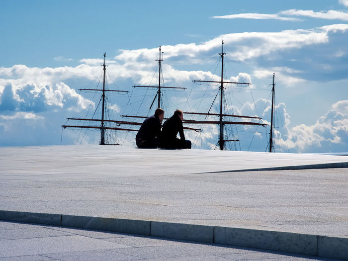 Friends sitting at pier against mast