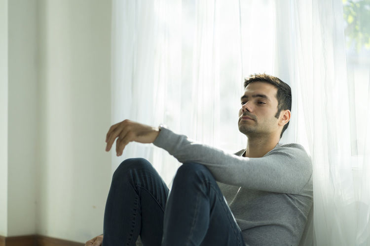 Depressed man sitting by curtain at home
