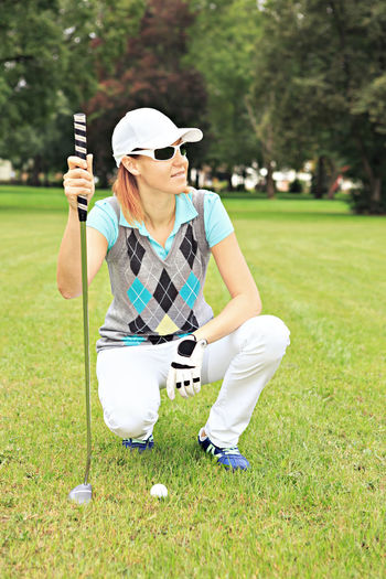 female golf player with a golf club on the course Action, Activity, Bag, Ball, Clubs, Course, Driver, Females, Field, Fun, Girl, Golfer, Golfs, Grass, Greens, Hobby, Iron, Outdoors, People, Play, Playing, Putting, Sports, Summer, Swing, Tee, Vacations, Woman, Women, Young Activity Casual Clothing Front View Full Length Glasses Golf Golf Club Golf Course Golfer Grass Green - Golf Course Hat Holding Leisure Activity Lifestyles One Person Outdoors Plant Real People Sunglasses Young Adult
