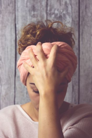 Stressed young woman with head in hand against wooden wall