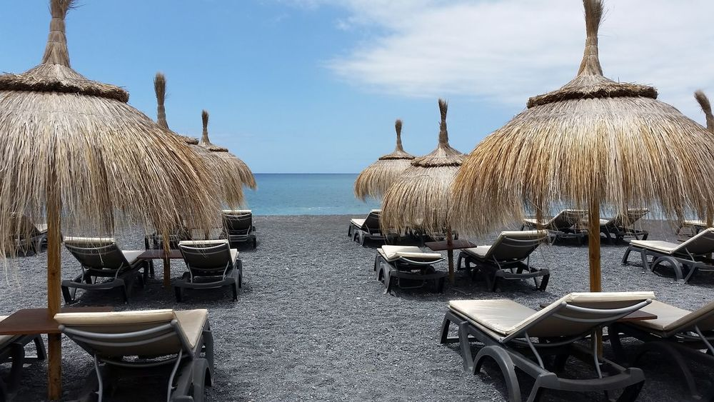 horizon over water in front to the atlantic ocean for a row of straw umbrellas with nobody. Order and freshness Atlantic Ocean Absence Beach Chair Cloud - Sky Day In A Row Land Nature No People Order Outdoors Parasol Perfection Roof Row Sea Seat Side By Side Sky Straw Umbrellas Tenerife Thatched Roof Umbrella Water