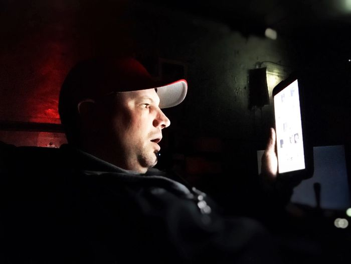 Man using digital tablet while sitting in darkroom