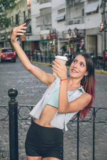 Portrait of young woman using mobile phone in city