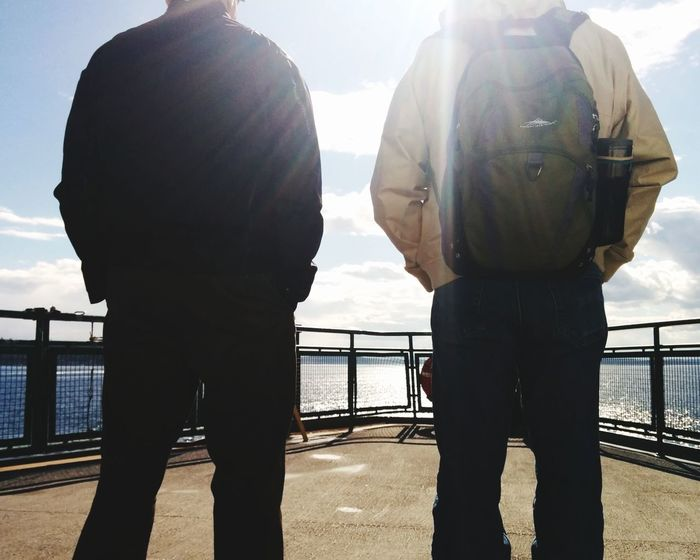 Two People Sunlight Railing People Back Lit Togetherness Silhouette Only Men Men Sky Outdoors Sea Sea And Sky Traveling Home For The Holidays Travel Adults Only Adult River Day Full Length Bridge - Man Made StructureNo Faces Traveling Home For The Holidays No Fac The Great Outdoors - 2017 EyeEm Awards