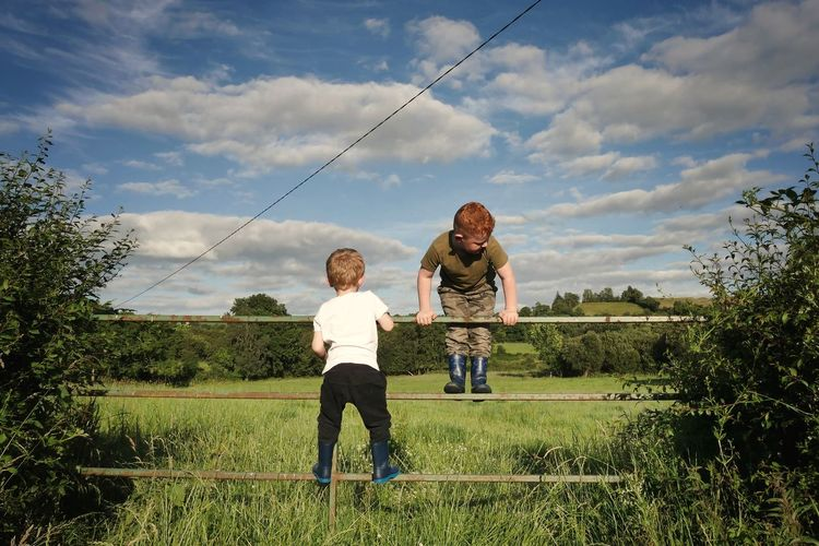 Full length of brothers on fence at grassy field against sky