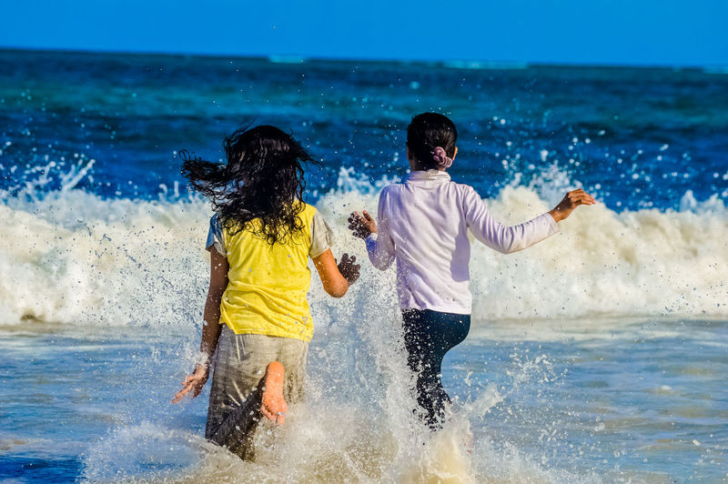 Children Playing In Water At Beach