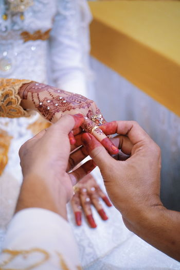 Close-up of couple holding hands during wedding