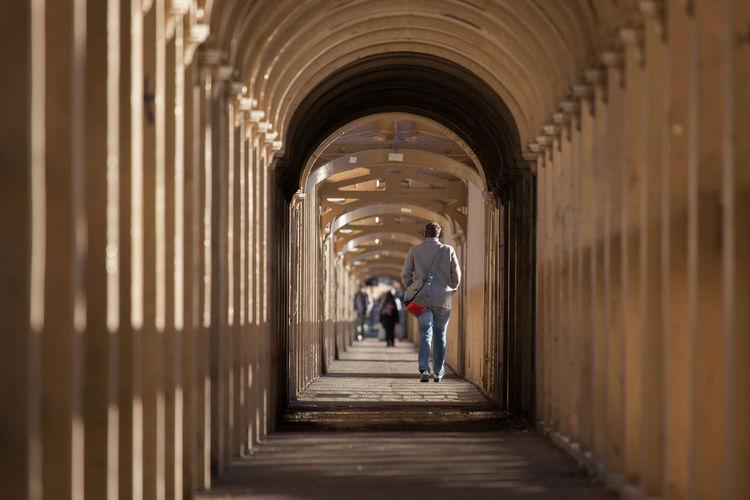 People Walking In Corridor Of Building