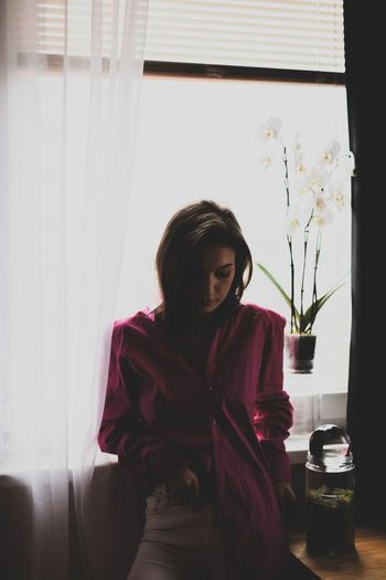 Young woman looking at window sill at home