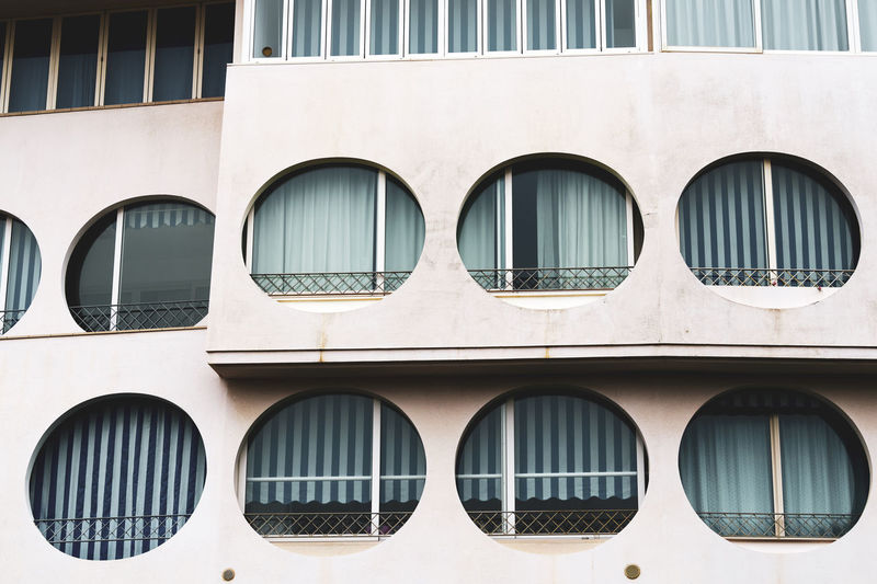building facade close up Porthole Flat House Modern Man Made Structure Residential Building Landscape City Life Front View Close Up Residential District Facades Apartment Buildings Apartment Construction Cement Geometric Shape Shapes And Forms Structures Design Architecture Urban City White Background Blue Glass - Material Curtains Striped Round Window Building Exterior