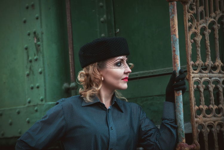 Beautiful woman wearing hat while standing by old train