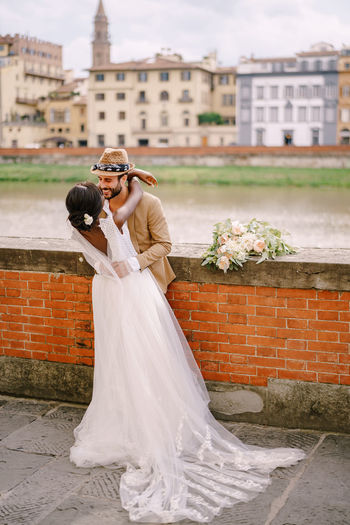 Couple embracing while standing by wall against building