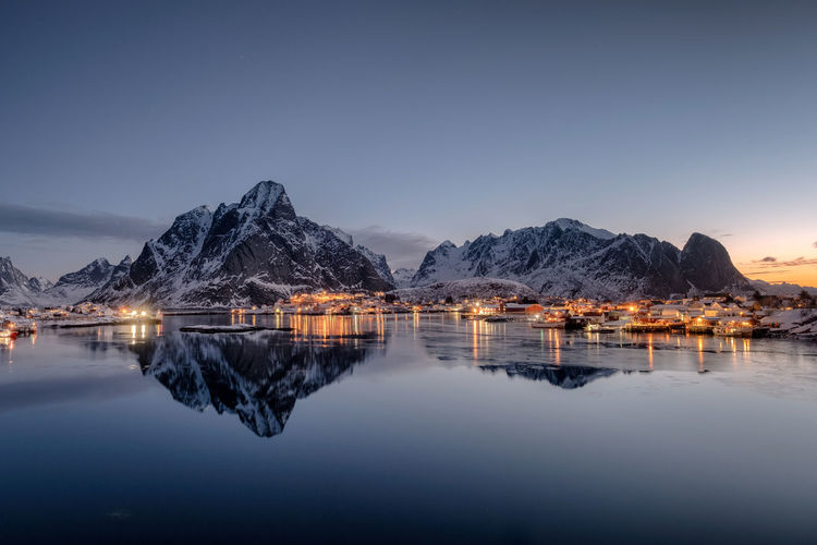 Fishing village illumination with mountain range reflection on coastline at dawn. Lofoten islands, Norway Water Sky Scenics - Nature Reflection Mountain Tranquility Beauty In Nature Tranquil Scene Lake Mountain Range Waterfront Copy Space Nature No People Idyllic Clear Sky Winter Non-urban Scene Lofoten Norway Scandinavia Snow Winter
