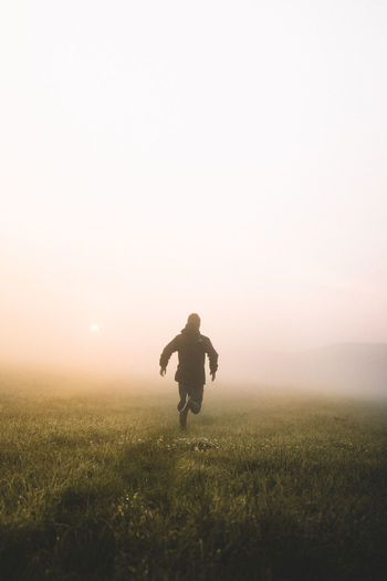 Rear view of man running on grassy field during foggy sunrise