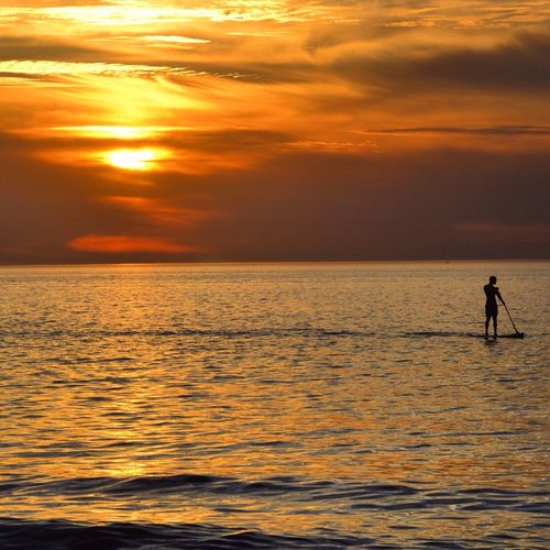 Silhouette man paddleboarding at sea against sky during sunset