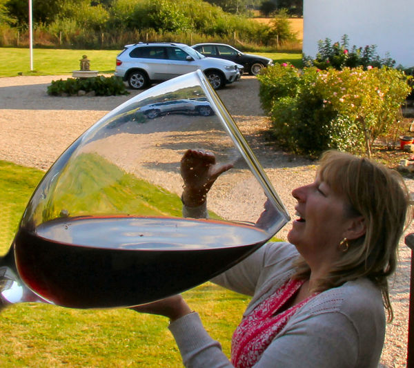 Optical illusion of woman drinking red wine from large glass