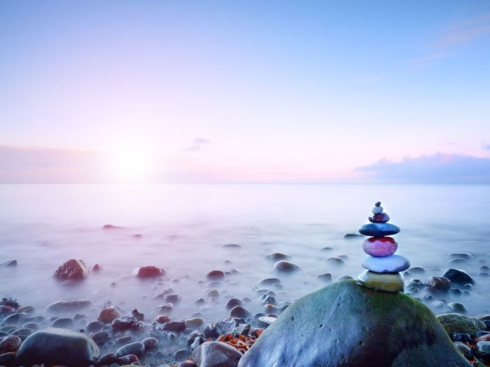 Balanced stone pyramide on shore of blue water of ocean. blue sky in water level mirror.