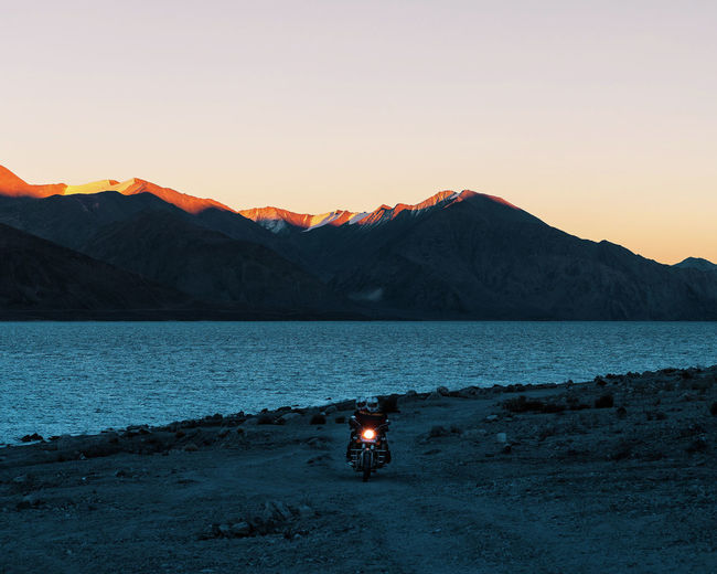 People Riding Motorcycle By Lake Against At Sunset