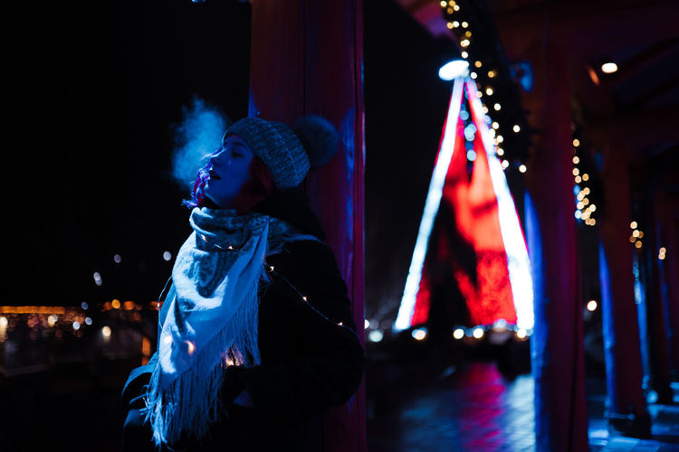 Woman looking at illuminated stage at night