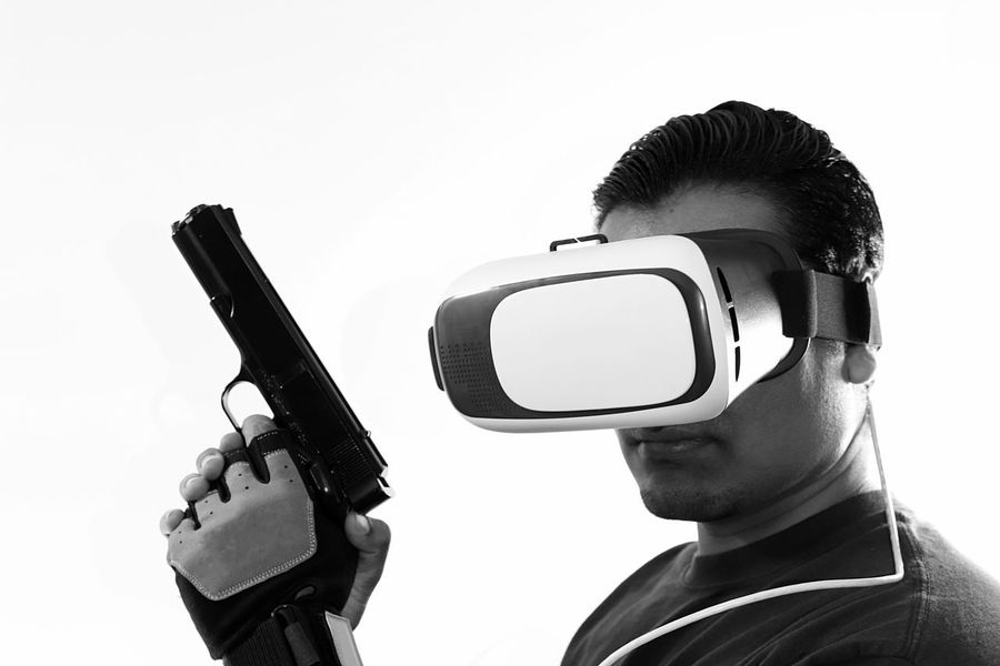 Young man with virtual reality headset holding gun wearing gloves with gun in hand black and white Console Display Futuristic Gamer Gaming Glasses Gloves Goggles Gun Headset Innovation New Pistol Playing Riffle Role Playing Game Shooter Shooting Technology Virtual Virtual Reality War Weapon White Background Wireless Technology