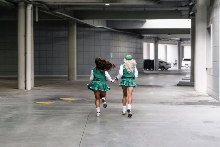 Rear View Of Female Friends Running In Parking Garage