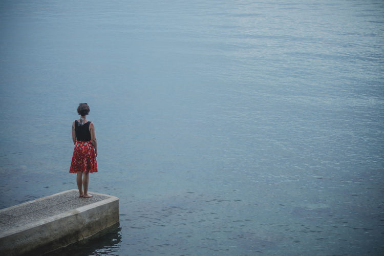 Rear view of woman standing by sea